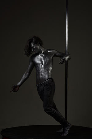 Fashion shot of young sexy mysterious athlete. Man with nude torso covered with shimmering silver paint, dark background. Macho with naked chest, athlete, sportsman hold metallic pole. Fashion concept Standard-Bild - 101616526