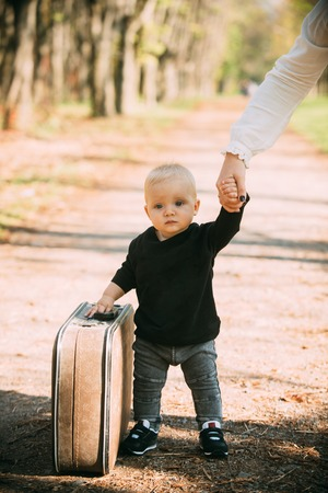 Travelling child carry suitcase on natural landscape. Travelling baby boy travel with vintage bag with mothers hand. Stockfoto