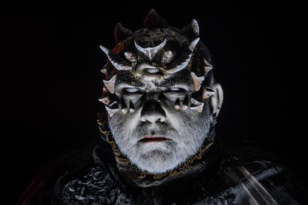 Alien, demon, sorcerer makeup. Horror and fantasy concept. Man with third eye, thorns or warts. Demon on black background, close up. Senior man with white beard dressed like monster in darkness.