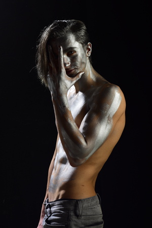 Man with nude torso covered with shimmering silver paint, black background. Guy with long hair posing mysteriously. Attractive sexy macho hides his face. Athletic figure concept. Banco de Imagens
