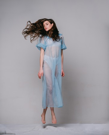 Lady in transparent blue nightie and white lingerie fly above bed, grey background. Woman with long curly hair wears tender pajama. Girl on calm face jump on bed. Femininity concept.