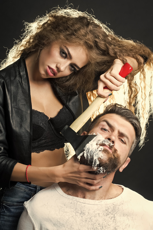 Woman shaving handsome bearded man 写真素材