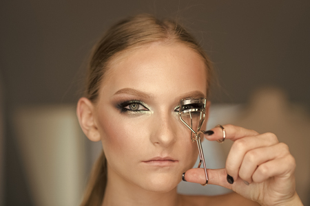 Woman use eyelash curler for eye makeup. Woman curl lashes with beauty tool, look. Model with curly long eyelashes, beauty. Fashion makeup for glamour girl, visage course