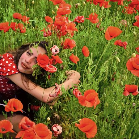 Woman in poppy flower field, harvest.