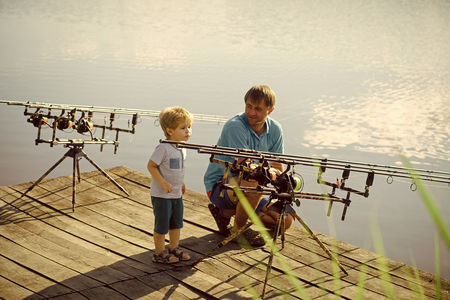 Man and little boy spending time outdoor and fishing