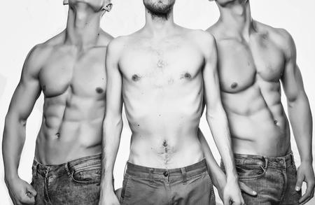 Thin torso between muscular men