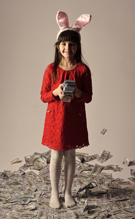 small girl child in bunny ears with many dollars money.
