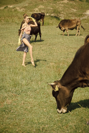 Cow, woman in countryside pasture, ecology. Stock Photo