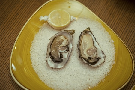 Seafood and Mediterranean cuisine. Oyster with lemon and crushed ice. healthy delicacy with omega 3 vitamin. Dieting and health. eating fresh oyster shellfish in luxury restaurant