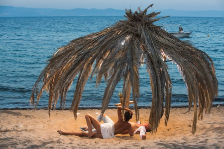 Young happy couple sitting on a sand by sea and enjoying each other under palm tree