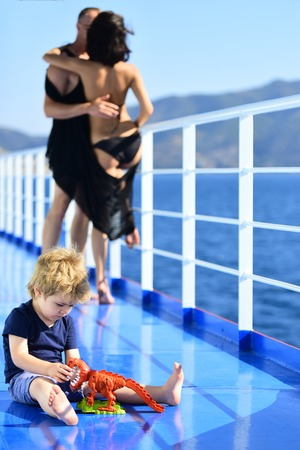 Child play with toys at father and mother. child with kissing parents on yacht in summer