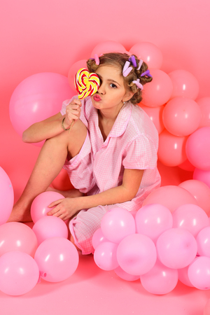 Diet, birthday, punchy pastels, beauty. Little girl with candy lollipop. Party balloons, kid in curlers, pajama fashion. Childhood, happiness, sweet dreams. Small girl child eat lollipop on pink. Standard-Bild