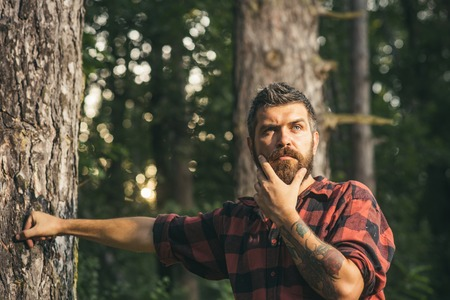 Thoughtful bearded man standing next to tree. Curious lumberjack holding his chin. Hipster wandering in nature, environment concept. Фото со стока