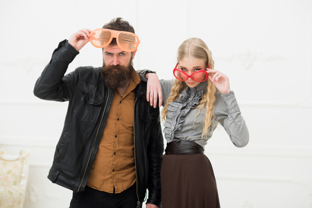 Stylish couple in huge orange glasses posing in studio. Man with nice beard and mustache hugging blond attractive girl. Fashion shooting. crazy fun couple
