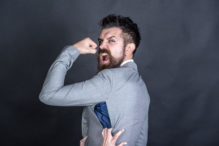 Angry guy bought counterfeit or fake brand. Man with beard wears jacket with hole on dark background. Hipster chose small size jacket, seam torn with female hands. Bad quality of clothes concept. Stock Photo