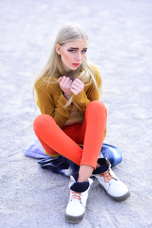 Young blond model with straight hair in bright outfit sitting on street with legs crossed and holding her arms crossed at her chest.