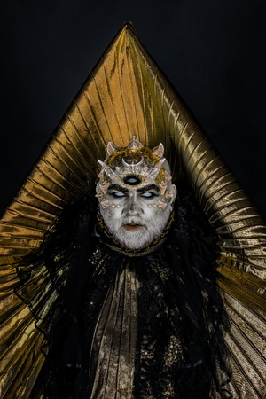 Man with third eye, thorns or warts. Demon with golden collar on black background. Senior man with white beard dressed like monster. Alien, demon, sorcerer makeup. Horror and fantasy concept. Stock Photo