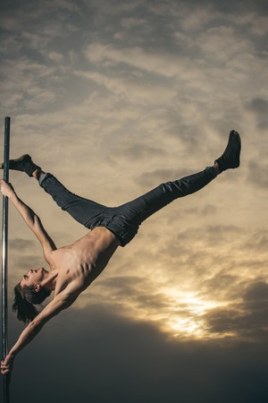 A young man sport is pole dancing at sunset.