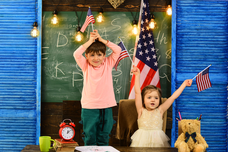 Help with homework is widely required among schoolkids now. Learning English language in USA. English female student with the American flag at the background.