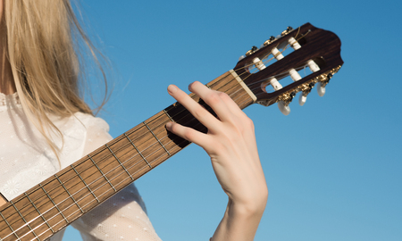 Guitar with fingers strumming strings. Guitar instrument with neck fretboard and headstock on sunny blue sky. Stock Photo