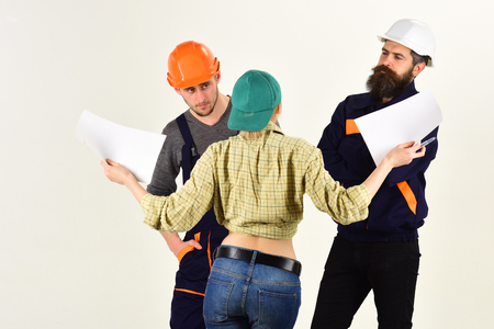 Brigade of workers, builders in helmets, repairers and lady discussing contract, white background, copy space. Technical task concept. Brigadier, foreman speak about terms of repair, renovation. Stock Photo