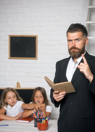 Literature lesson and reading grammar book. literature lesson with small girls and bearded man teacher Stock Photo