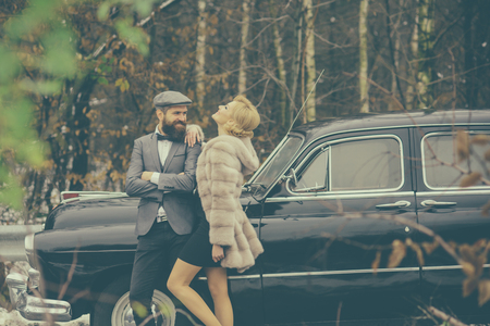 Couple in love on romantic date. Escort of girl by security. Travel and business trip or hitch hiking. Retro collection car and auto repair by mechanic driver. Bearded man and sexy woman in fur coat