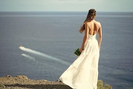 Pretty girl or beautiful bride on blue sea