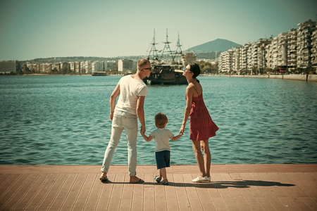 Mother and father going to kiss near their child. Happy family spend time together, sea background. Parents with son stand on seafront, rear view. Family vacation concept. Reklamní fotografie