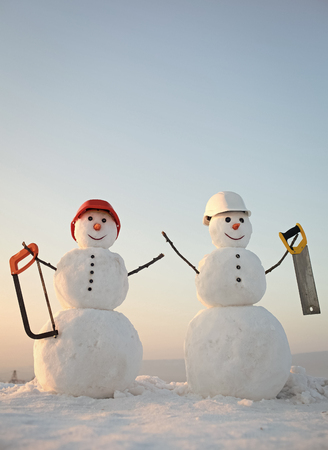 New year snowman from snow with saw. Stock Photo