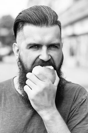 Bearded man eating apple