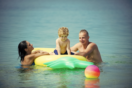 Family spend time together and having fun. Cute child boy sits on air mattress pineapple shaped in the ocean, sea, with parents. Family vacation concept. Father and mother near mattress swim with son.