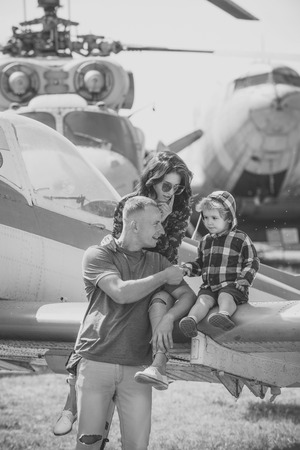 Mother, father and excited child sit on planes wing in aviation museum. Development and upbringing concept. Happy family on excursion, helicopter or plane on background, sunny day.