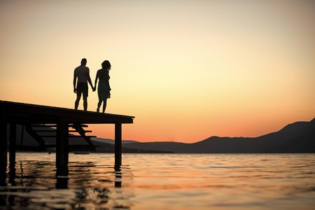 Silhouette of sensual couple stand on pier with sunset above sea surface on background. Couple in love on romantic date in evening at dock, copy space. Romance and love concept. Banque d'images - 101221289