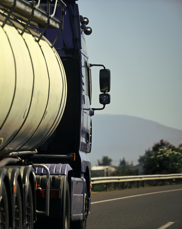 Ð¡argo van, truck, kamion transports goods or items between countries. International transportation concept. Camion with cistern rides along the road on sunny day, rear view.