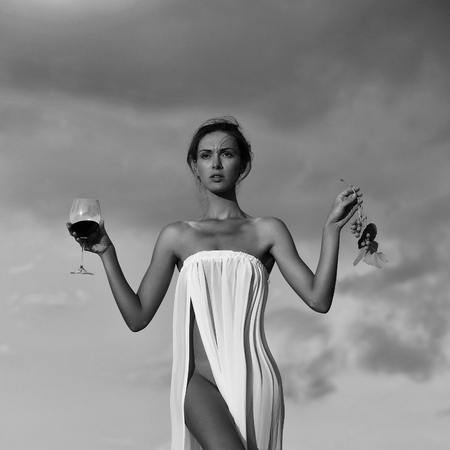 girl or woman in white sexy dress denuded with red wine in glass and grapes on nature over blue sky 写真素材