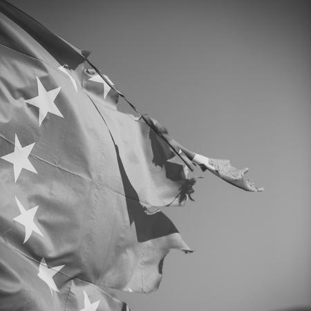 European union twelve star flag torn and with knots in wind on blue sky background, close up. Flag is torn off at side, symbol of problems, decay, disintegration, decomposition, breakdown Stock Photo