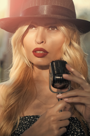 music and karaoke. singer girl in hat with mic. beauty and fashion, retro and jazz. live performance, studio, concert, show. woman with blonde hair and red lips sing in microphone.