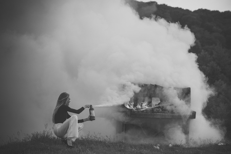 Fire and smoke on grunge instrument. fire and white smoke at burning piano and girl firefighter
