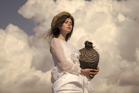 Girl with wicker wine bottle on cloudy sky. Woman in white dress and wreath on brunette hair. Harvesting and winemaking. Summer vacation, holidays and celebration. Winery tour concept. Фото со стока - 106748495