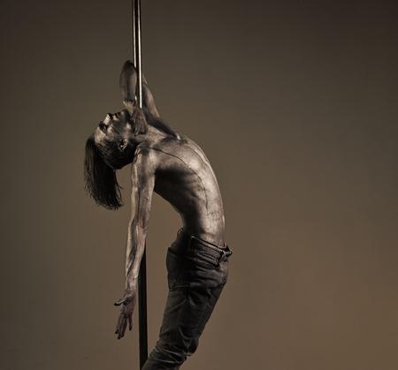 Artistic guy hanging on metallis pole. Performance concept. Standard-Bild - 101295804