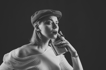 Blonde lady looks like suspicious detective. Detective concept. Girl thinking about investigation, holds flask and smoking cigar, copy space. Woman on mysterious face wears kepi, dark background
