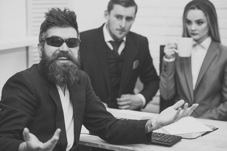 Man with beard in sunglasses smiling, bosses, coworkers, colleagues on background. Man happy hired for work in office. Successful job interview concept. Coffee break with colleagues in office