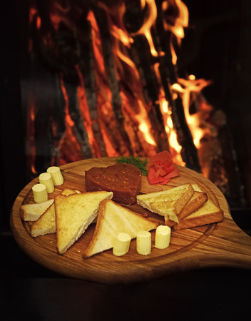 Tatar beefsteak served in shape of heart on round wooden board. Bread, toast and butter around beefsteak on board. Restaurant dish concept. Dish appetizing decorated with dill, fire on background
