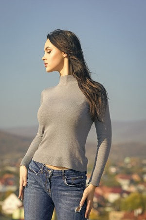 Fashion model with fit body pose in sweater jeans on sunny day on natural landscape. Wanderlust, lifestyle, travelling, concept.