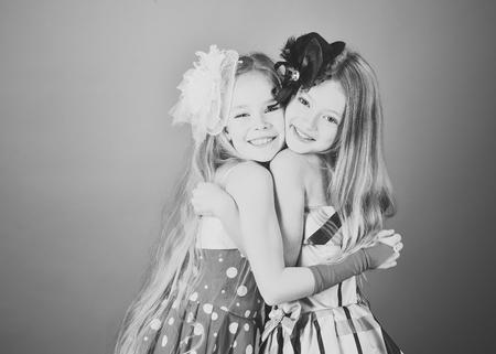 Little girls in fashionable dress, prom. little girls sisters embrace.