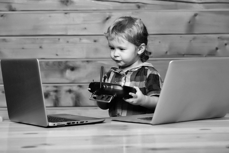 Cute baby boy child with blond curly hair plays on two phones and laptop computers on wooden background holds black console with antenna Banque d'images - 105438414