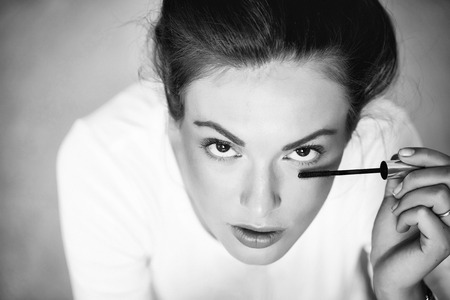 sexy woman or girl portrait with pretty face and brunette hair dyeing eyelashes with mascara brush as fashionable makeup in white shirt 版權商用圖片