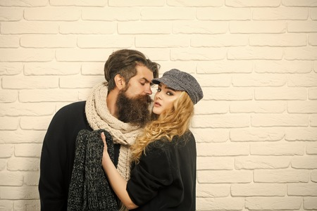 Relations of girl and guy in autumn. Man with beard and girl with long hair. Boyfriend and girlfriend on brick wall background. Couple in love of fashionable man and woman. Love and romance.