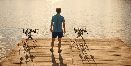 Angler man stand on wooden pier, back view. Fisherman fishing with spinning rods, reels at lake water. Summer vacation, adventure, activity. Fishing, angling, hobby, sport Banque d'images - 101295998